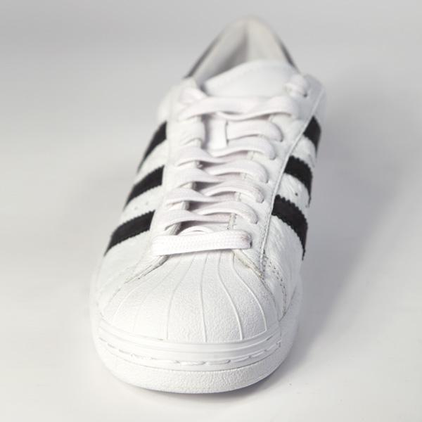 Deportivo blanco con lineas laterales negra.